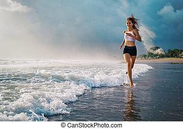 Active sporty woman run along sunset ocean beach. Sports...