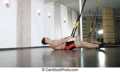Man is engaged in trx exercises in the studio 4k