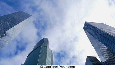Modern mirrored building and fast moving white clouds on the...