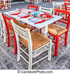 Alfresco restaurant with white and red table and chairs,...