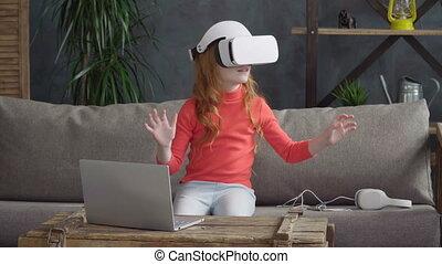 Little girl in VR headset - Little girl is sitting on the...