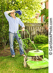 Man mowing lawn - Man taking a break while mowing lawn on...