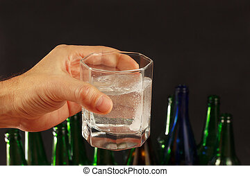 Hand with a glass of water and effervescent tablet of a...