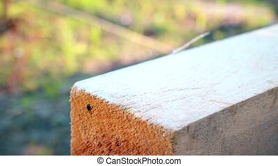 A framing square is used to mark a wooden beam for cutting...