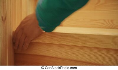 Hands of man polishing wooden steps of staircase boards...