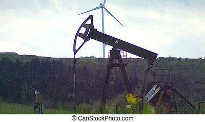 oil well with pump jack and Wind power plant on the mountain in background