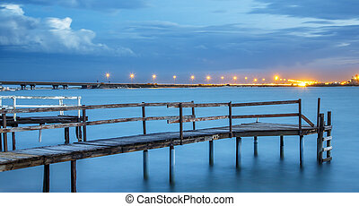 Old Jetty on a River with City Lights in the Background -...