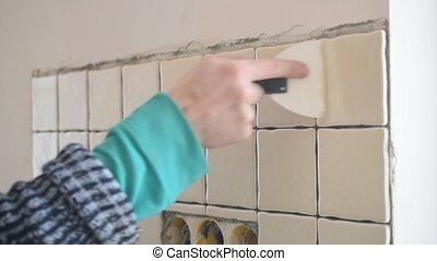 Tile worker filling gaps between tiles with grout - Hands of...