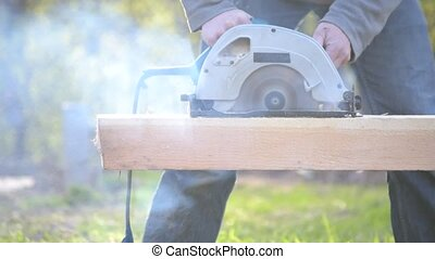 Sawing wooden beam with a blunt, not sharp circular hand...