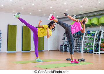 Fitness female instructors practicing sidekick exercise...