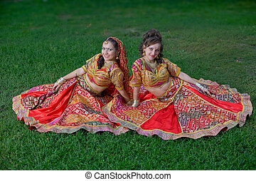 young indian smiling girls sit on grass