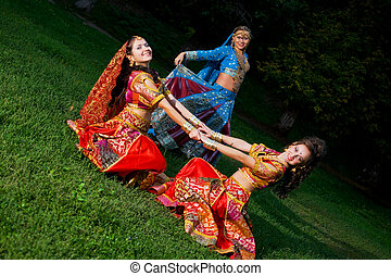 Young woman traditional indian costume, dance on grass
