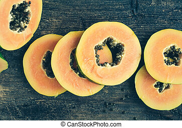Slices of sweet papaya on wooden background - Slices of ripe...