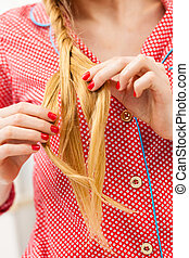 Closeup of woman doing braid on blonde hair
