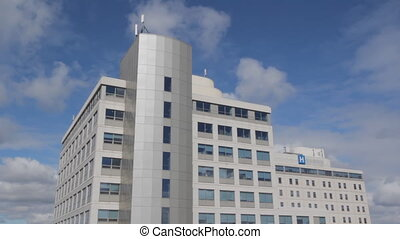 Hospital with timelapse clouds. - Hospital with blue sky and...