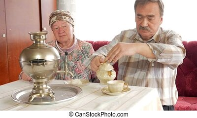 An elderly couple prepares tea with a vintage Russian kettle samovar. A man with a mustache pours tea for his wife