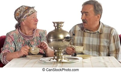 An elderly couple is drinking tea from a vintage Russian...