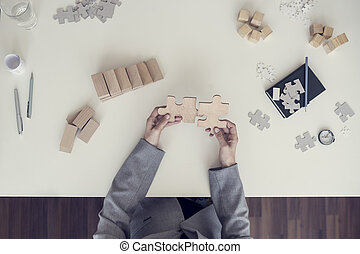 Top view of female hands assembling two wooden puzzle pieces