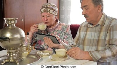 Elderly couple drink tea from a vintage Russian teapot samovar and watch a photo in the tablet. A man with a mustache and a woman discussing the image.