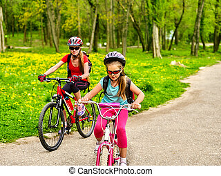 Mother and daughter on bicycle. Bikes cycling family. Happy...
