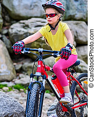 Child on bicycle ride mountain. Girl traveling in summer park.