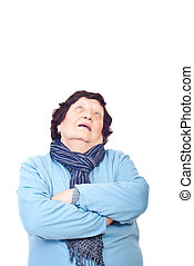 Older woman looking up to copy space and standing with arms...