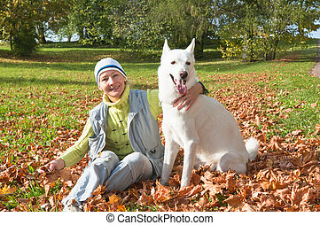 The woman with a white dog in autumn park