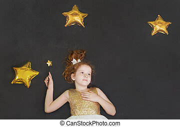 Cute princess girl dreaming on a chalkboard background with...