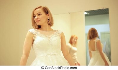 shop assistant is helping for beautiful bride trying on wedding dress in bridal boutique in fitting room