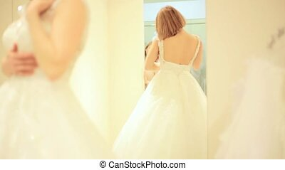 Elegant bride trying wedding gown in bridal shop in fitting...