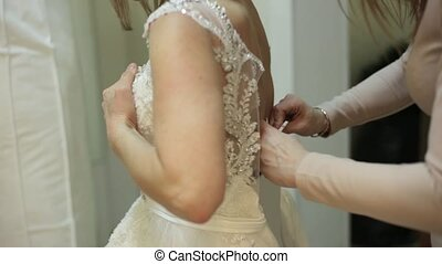 beautiful girl trying on wedding dress in bridal boutique, shop assistant is helping for bride in fitting room