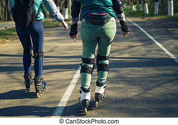Two girls on roller skates ride along the road next to each other
