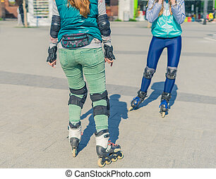 Two girls rollers meet each other in the park