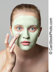 Girl with green cream on face. - Beautiful young woman...
