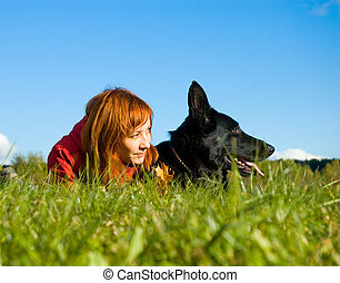 woman with her dog on meadow.