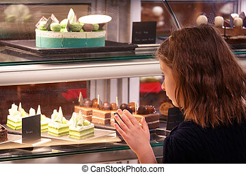 Little girl in confectionary shop looking at the display. Sweet treats variety. Small business and child concept
