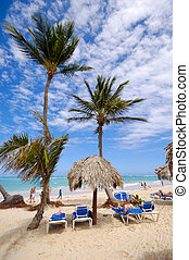 Sunbeds and parasol on an exotic beach. Dominican Republic,...