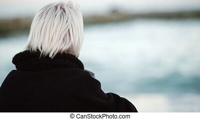 On the beach, he drinks coffee. He looks into the distance, straightens his hair. View from the back