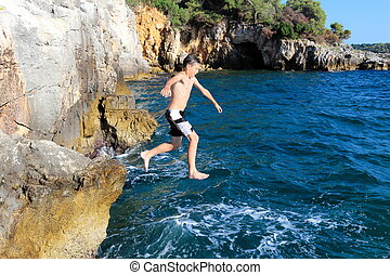 boy jumps from cliff in the ocean
