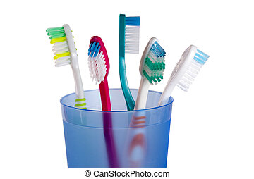 Toothbrushes in blue glass isolated on white background