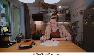 Young businesswoman with documents sitting at the table and working with papers. Overtime work at home.