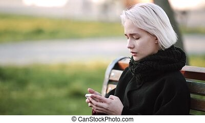 Blonde girl outside Looks at the smartphone on a bench Plays an active 3D game on smartphone Smiles