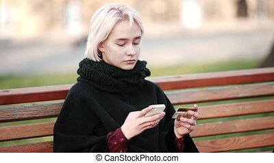 Sad Blonde girl outside Performs transactions gold payment debit credit card to the smartphone