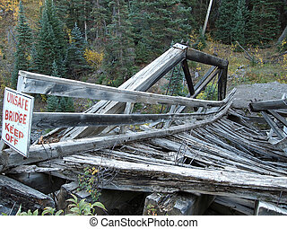 Bridge with Sign - An old wooden road bridge collapses into...