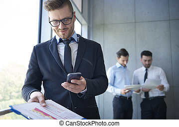Man in suit using a smartphone