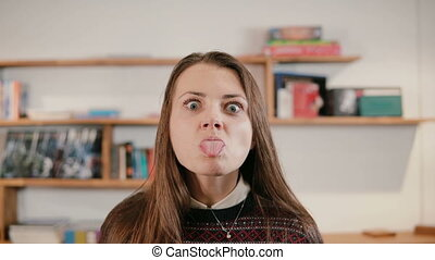 Portrait of young woman makes silly face, puts out the tongue. Girl chews gum and laughs. Employee at modern office.