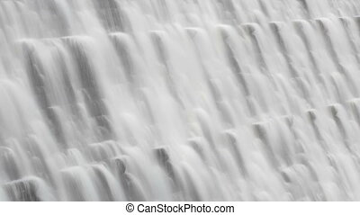 Timelapse water flowing over a dam.