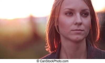 Portrait of young pensive woman at the park, looking into the distance in the rays of the setting sun, close-up