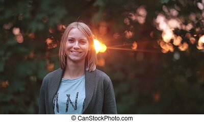 Young beautiful woman standing at park in the rays of the setting sun, smiling and laughing, looking to the camera