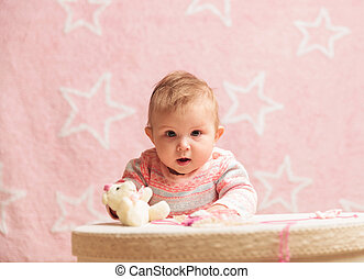 baby girl standing near toy box with little bear on - cute...